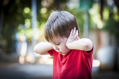 enfant mettant ses mains sur ses oreilles